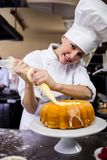 Female chef piping a cake in kitchen. At hotel royalty free stock photos