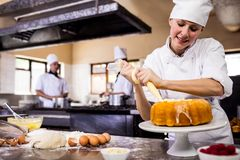 Female chef piping a cake in kitchen. At hotel royalty free stock photo
