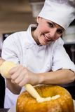 Female chef piping a cake in kitchen. At hotel stock photo