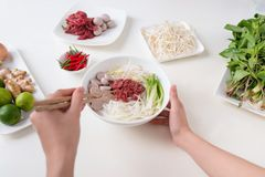Female chef prepare traditional Vietnamese soup Pho bo with herb Royalty Free Stock Photography