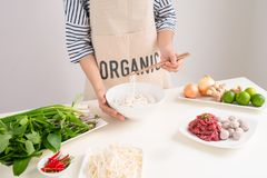 Female chef prepare traditional Vietnamese soup Pho bo with herb Royalty Free Stock Photos