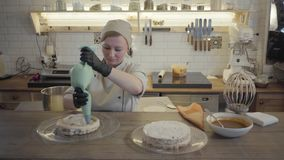 The female chef preparing a cake in the restaurant kitchen close-up. The cook decorating the top cake layer from airy stock video footage