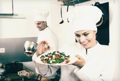 Female chef preparing fresh salad. Portrait of positive young women in cook uniform preparing fresh green salad Stock Photography