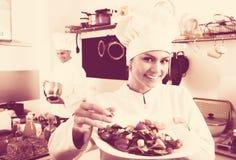Female chef preparing fresh salad. Portrait of positive young women dressed as chef preparing fresh green salad in kitchen interior Stock Photos
