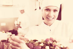 Female chef preparing fresh salad. Portrait of smiling young woman dressed as chef preparing fresh green salad Stock Photo
