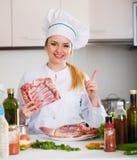 Female chef preparing lamb parts at kitchen table Stock Photos