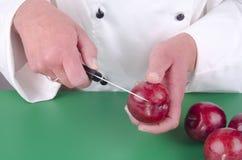 Female chef preparing a plum Stock Photo