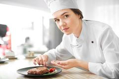 Female chef preparing tasty steak. In kitchen stock photo