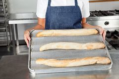 Female Chef Presenting Baked Loafs Royalty Free Stock Image