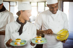 Female chef presenting dessert plates Royalty Free Stock Images