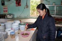 Female chef process fried cicadas Royalty Free Stock Photo