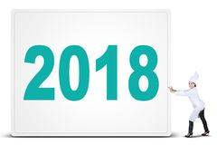 Female chef pushing placard with number of 2018. Portrait of Indian woman wearing the chef clothes pushing a placard with number of 2018, isolated on white Royalty Free Stock Photo