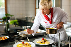 Female chef in a restaurant or hotel kitchen cooki. Ng delicious food, she is decorating the dishes Stock Images