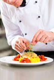 Female Chef in restaurant kitchen cooking. Chef in hotel or restaurant kitchen cooking, he is finishing a dish on plate Royalty Free Stock Photo