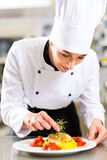 Female Chef in restaurant kitchen cooking. Female Chef in hotel or restaurant kitchen cooking, she is finishing a dish on plate stock image