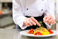 Female Chef in restaurant kitchen cooking. Female Chef in hotel or restaurant kitchen cooking, only hands, she is finishing a dish on plate Royalty Free Stock Photo