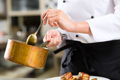 Female Chef in restaurant kitchen cooking. Female Chef in hotel or restaurant kitchen cooking, only hands to be seen, she is working on the sauce as saucier Stock Photography