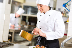 Female Chef in restaurant kitchen cooking. Female Chef in hotel or restaurant kitchen cooking, she is working on the sauce as saucier Stock Photo