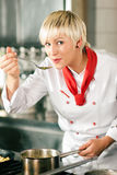 Female Chef in a restaurant kitchen tasting stock photography