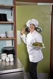 Female chef in restaurant with salad plate. Chef working in restaurant standing at kitchen doorway with gourmet salad place royalty free stock image