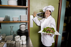 Female chef in restaurant with salad plate. Chef working in restaurant standing at kitchen doorway with gourmet salad place stock photo