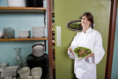 Female chef in restaurant with salad plate Stock Photos