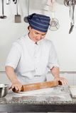 Female Chef Rolling Dough In Kitchen Stock Photos