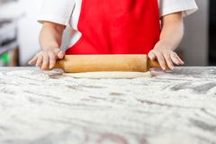 Female Chef Rolling Dough At Messy Counter Royalty Free Stock Image