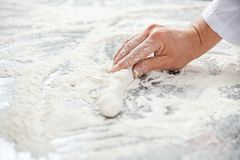 Female Chef's Hand Holding Dough At Messy Counter Stock Photo