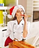 Female chef in Santa hat  holding  food. Female chef in Santa hat baking baguette bread Royalty Free Stock Images