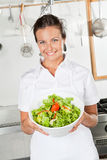 Female Chef Showing Vegetable Salad. Portrait of happy female chef showing vegetable salad in industrial kitchen Royalty Free Stock Photo