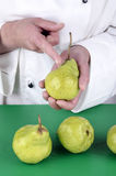 Female chef shows with her index finger on a pear Royalty Free Stock Images
