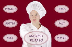Female chef shows how to make mashed potato Royalty Free Stock Photography