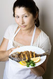 Female chef shows sea bream fish Royalty Free Stock Images