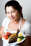 Female chef shows sea bream fish Royalty Free Stock Photography