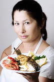 Female chef shows sea bream fish Royalty Free Stock Image