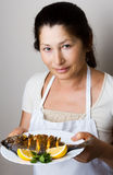 Female chef shows sea bream fish Royalty Free Stock Photos