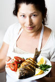 Female chef shows sea bream fish Stock Images