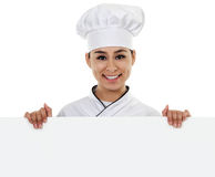Female Chef with Sign. Stock image of female chef holding blank sign with copy space royalty free stock photos