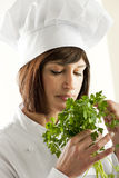 Female Chef Smelling Parsley Royalty Free Stock Photography