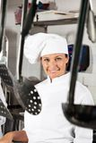 Female Chef With Spoons Hanging In Foreground Royalty Free Stock Image