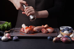 A female chef sprinkles fresh raw chicken drumsticks on a dark background with a mixture of peppers. Nearby lie the. Ingredients for cooking: shallots, blue Stock Photography