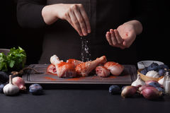 A female chef sprinkles fresh raw chicken drumsticks on a dark background with sea salt. Nearby lie the ingredients for. Cooking: shallots, blue plums, garlic Royalty Free Stock Images