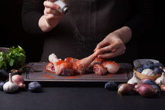 A female chef sprinkles fresh raw chicken drumsticks on a dark background with sea salt. Nearby lie the ingredients for. Cooking: shallots, blue plums, garlic Royalty Free Stock Photos