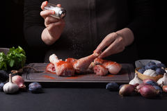 A female chef sprinkles fresh raw chicken drumsticks on a dark background with sea salt. Nearby lie the ingredients for. Cooking: shallots, blue plums, garlic Royalty Free Stock Image