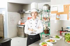 Beautiful Cook Standing In Commercial Kitchen. Female chef standing arms crossed by prepared food in kitchen royalty free stock image