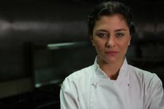 Female chef standing in commercial kitchen. Portrait of female chef standing in commercial kitchen stock photos