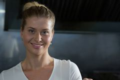 Female chef standing in the kitchen. Portrait of female chef standing in the kitchen royalty free stock image
