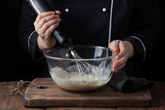 Female chef stirring his batter with a whisk on a black background royalty free stock photography