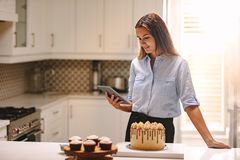 Female chef with tablet pc in kitchen. Woman standing in the kitchen using digital tablet with pastry items on the kitchen counter. Female chef looking at her royalty free stock photos